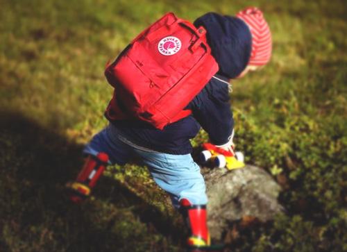 Mochila kanken para niños roja en la espalda de un crío que juega sobre una roca