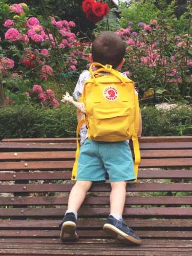 niño con una original mochila infantil Kanken subido a un banco de espaldas
